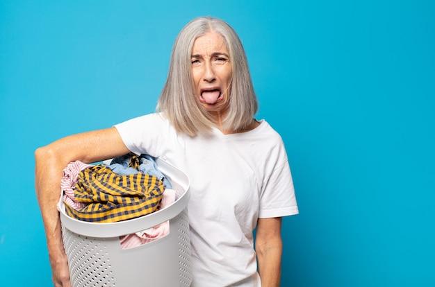 Vrouw van middelbare leeftijd die walgt en geïrriteerd voelt, tong uitsteekt