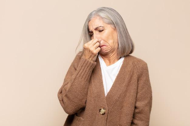Vrouw van middelbare leeftijd die walgt en neus vasthoudt om te voorkomen dat ze een vieze en onaangename stank ruikt