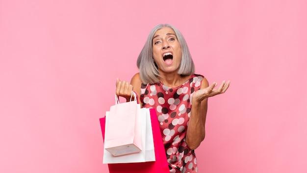 Vrouw van middelbare leeftijd die wanhopig en gefrustreerd geïsoleerd kijkt