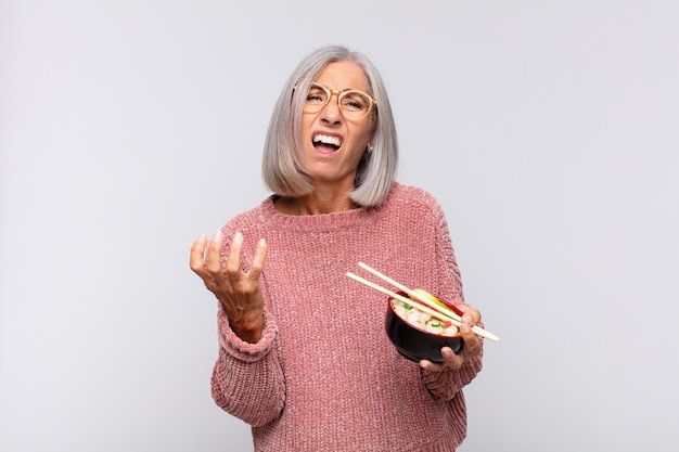 Vrouw van middelbare leeftijd die wanhopig en gefrustreerd, gestrest, ongelukkig en geïrriteerd, schreeuwend en schreeuwend aziatisch voedselconcept kijkt