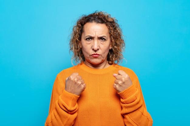 Vrouw van middelbare leeftijd die zelfverzekerd, boos, sterk en agressief kijkt, met vuisten klaar om te vechten in bokspositie