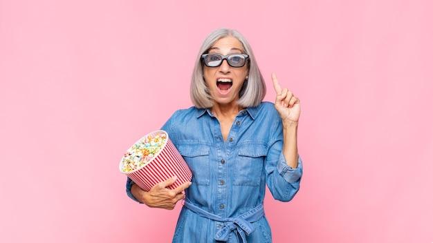 Vrouw van middelbare leeftijd die zich als een gelukkig en opgewonden genie voelt na het realiseren van een idee, opgewekt de vinger opstekend, eureka! film concept