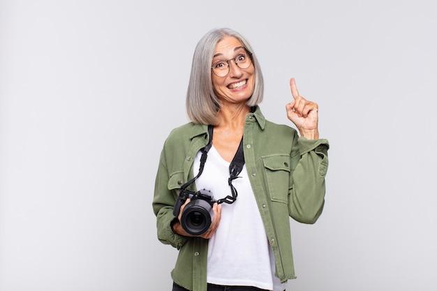Vrouw van middelbare leeftijd die zich als een gelukkig en opgewonden genie voelt nadat ze een idee heeft gerealiseerd