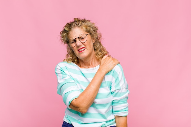Vrouw van middelbare leeftijd die zich angstig, ziek, ziek en ongelukkig voelt, pijnlijke buikpijn of griep heeft