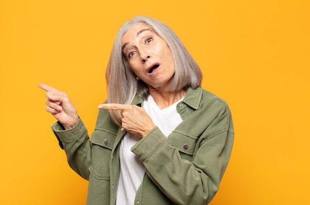 Vrouw van middelbare leeftijd die zich blij en verrast voelt, met een geschokte uitdrukking glimlacht en naar de zijkant wijst