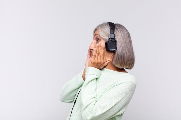 Vrouw van middelbare leeftijd die zich blij, opgewonden en verrast voelt, opzij kijkt met beide handen op het gezicht. muziek concept