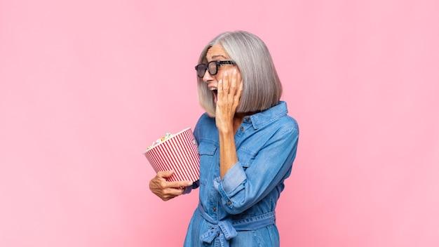 Vrouw van middelbare leeftijd die zich blij, opgewonden en verrast voelt