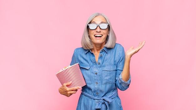 Vrouw van middelbare leeftijd die zich blij, opgewonden, verrast of geschokt voelt, glimlacht en verbaasd is over iets ongelooflijks filmconcept