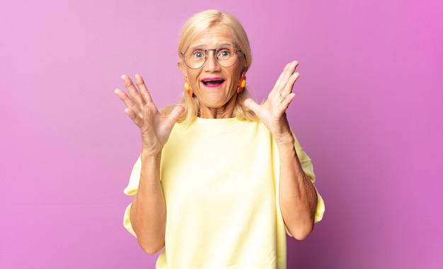 Vrouw van middelbare leeftijd die zich blij, opgewonden, verrast of geschokt voelt, glimlacht en verbaasd is over iets ongelooflijks