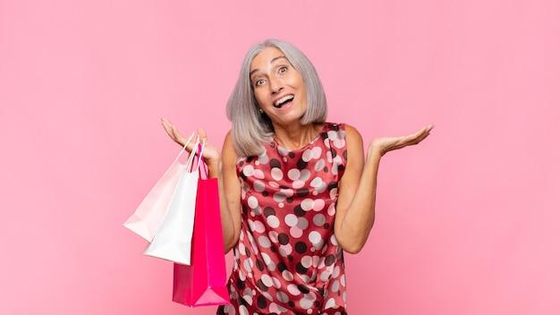 Vrouw van middelbare leeftijd die zich blij, opgewonden, verrast of geschokt voelt