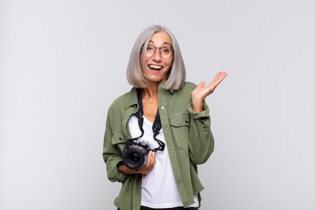 Vrouw van middelbare leeftijd die zich blij, verrast en opgewekt voelt, glimlachend met een positieve houding