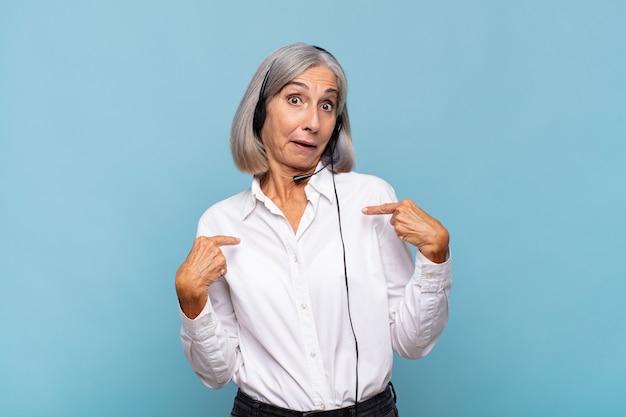 Vrouw van middelbare leeftijd die zich blij, verrast en trots voelt en naar zichzelf wijst met een opgewonden, verbaasde blik. telemarketeer concept