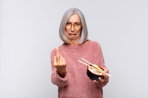 Vrouw van middelbare leeftijd die zich boos, geïrriteerd, opstandig en agressief voelt, de middelvinger wegknipt, aziatisch eten terugvecht