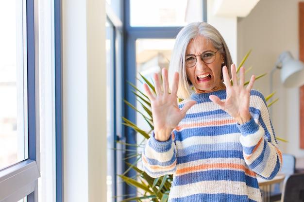 Vrouw van middelbare leeftijd die zich doodsbang voelde, deinsde terug en schreeuwde van afgrijzen en paniek, reagerend op een nachtmerrie