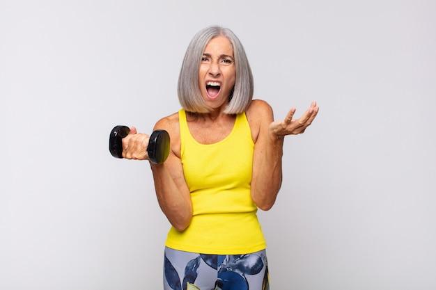 Vrouw van middelbare leeftijd die zich extreem geschokt en verrast, angstig en in paniek voelt, met een gestreste en geschokte blik. fitness concept