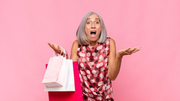 Vrouw van middelbare leeftijd die zich extreem geschokt en verrast, angstig en in paniek voelt, met een gestreste en geschokte blik met boodschappentassen