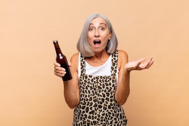 Vrouw van middelbare leeftijd die zich extreem geschokt en verrast, angstig en in paniek voelt, met een gestreste en geschokte blik met een biertje