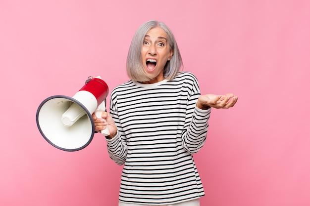 Vrouw van middelbare leeftijd die zich extreem geschokt en verrast, angstig en in paniek voelt, met een gestreste en geschokte blik met een megafoon