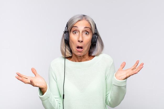 Vrouw van middelbare leeftijd die zich extreem geschokt en verrast, angstig en in paniek voelt, met een gestreste en geschokte blik. muziek concept