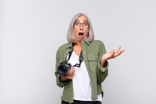 Vrouw van middelbare leeftijd die zich extreem geschokt en verrast, angstig en in paniek voelt, met een gestreste en geschokte blik