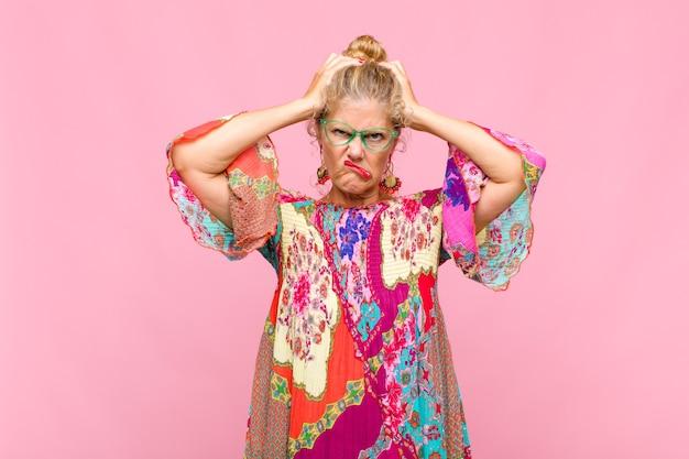 Vrouw van middelbare leeftijd die zich gefrustreerd en geïrriteerd voelt, ziek en moe is van mislukking, beu is met saaie, saaie taken