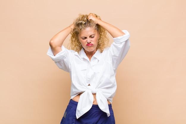 Vrouw van middelbare leeftijd die zich gefrustreerd en geïrriteerd voelt, ziek en moe van mislukking, beu is met saaie, saaie taken