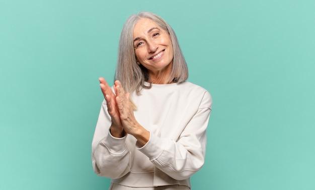 Vrouw van middelbare leeftijd die zich gelukkig en succesvol voelt, lacht en in de handen klapt, gefeliciteerd met een applaus