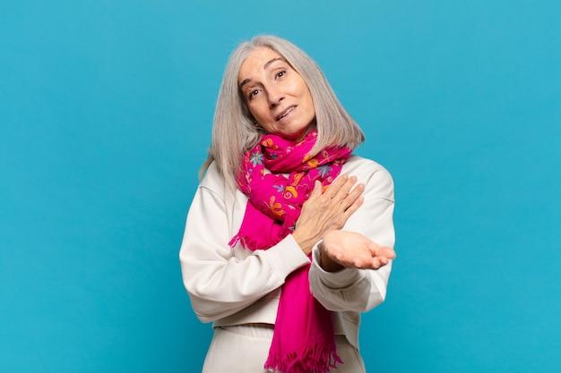Vrouw van middelbare leeftijd die zich gelukkig en verliefd voelt, glimlachend met de ene hand naast het hart en de andere vooraan gestrekt