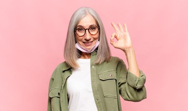 Vrouw van middelbare leeftijd die zich gelukkig, ontspannen en tevreden voelt en goedkeuring toont met een goed gebaar glimlachend
