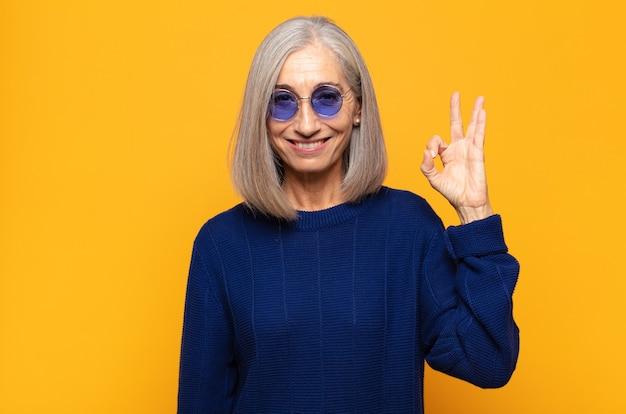 Vrouw van middelbare leeftijd die zich gelukkig, ontspannen en tevreden voelt, goedkeuring toont met een goed gebaar, glimlachend