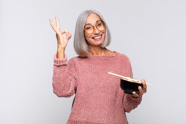 Vrouw van middelbare leeftijd die zich gelukkig, ontspannen en tevreden voelt, goedkeuring toont met oke gebaar, glimlachend aziatisch voedselconcept