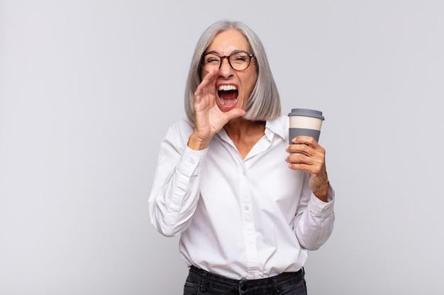 Vrouw van middelbare leeftijd die zich gelukkig, opgewonden en positief voelt, een grote schreeuw geeft met de handen naast de mond, koffieconcept roept