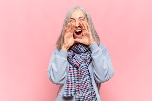 Vrouw van middelbare leeftijd die zich gelukkig, opgewonden en positief voelt, een grote schreeuw geeft met de handen naast de mond, roept