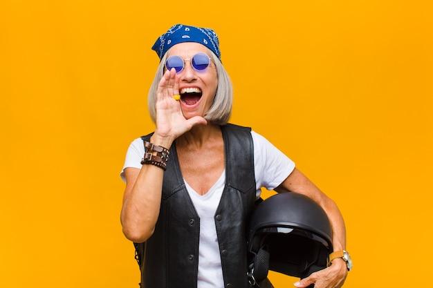 Vrouw van middelbare leeftijd die zich gelukkig, opgewonden en positief voelt, een grote schreeuw geeft met handen naast de mond, roept