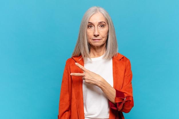Vrouw van middelbare leeftijd die zich gelukkig, positief en succesvol voelt, met hand die v-vorm over borst maakt, overwinning of vrede toont
