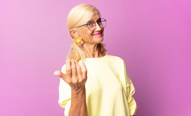 Vrouw van middelbare leeftijd die zich gelukkig, succesvol en zelfverzekerd voelt, voor een uitdaging staat en zegt: kom maar op! of je verwelkomen