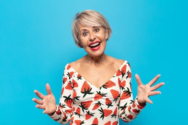 Vrouw van middelbare leeftijd die zich gelukkig, verbaasd, gelukkig en verrast voelt, zoals omg serieus te zeggen? ongelooflijk
