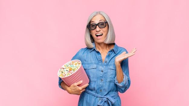 Vrouw van middelbare leeftijd die zich gelukkig, verrast en opgewekt voelt, glimlachend met een positieve houding, een oplossing of idee filmconcept realiserend