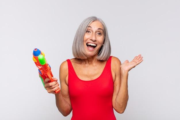 Vrouw van middelbare leeftijd die zich gelukkig, verrast en opgewekt voelt, lacht met een positieve houding, een oplossing of idee realiseert met een waterpistool
