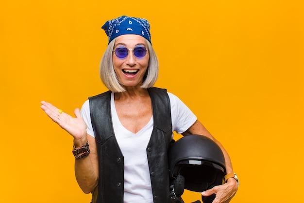 Vrouw van middelbare leeftijd die zich gelukkig, verrast en opgewekt voelt, lacht met een positieve houding, een oplossing of idee realiseert