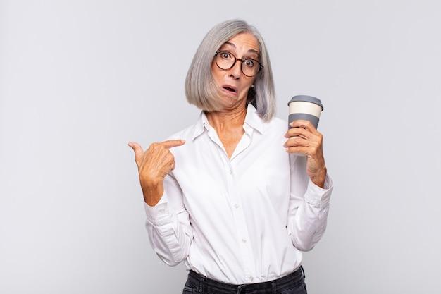 Vrouw van middelbare leeftijd die zich gelukkig, verrast en trots voelt en naar zichzelf wijst met opgewonden
