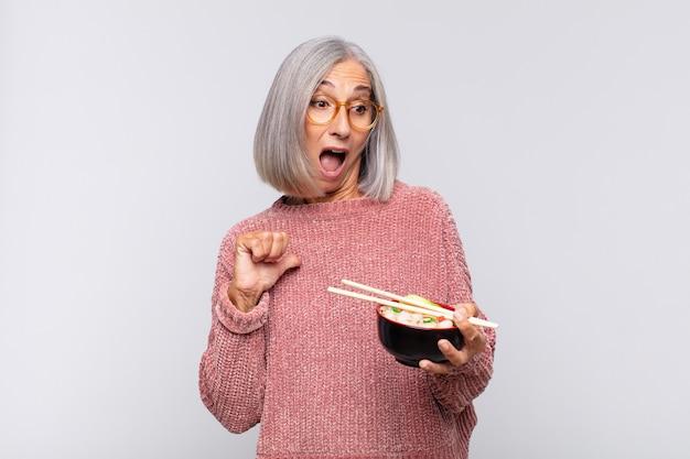 Vrouw van middelbare leeftijd die zich gelukkig, verrast en trots voelt, naar zichzelf wijst met een opgewonden, verbaasd blik aziatisch eten