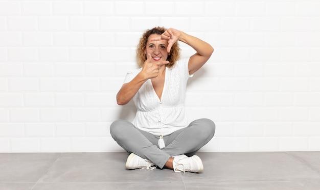 Vrouw van middelbare leeftijd die zich gelukkig, vriendelijk en positief voelt, lacht en een portret of fotolijst met handen maakt