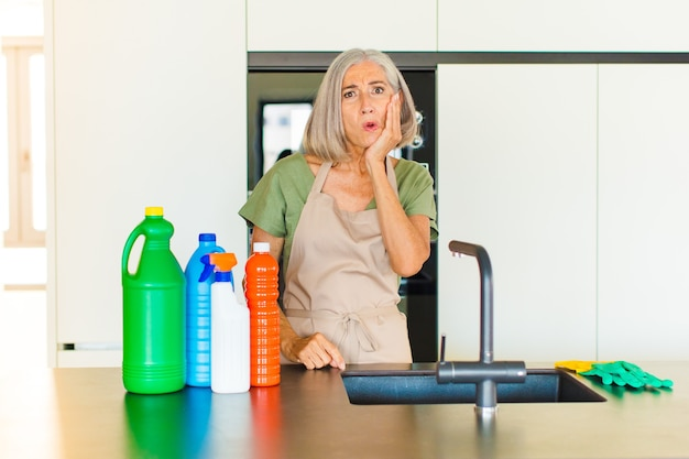 Vrouw van middelbare leeftijd die zich geschokt en verbaasd voelt terwijl ze met wijd open mond van aangezicht tot hand in ongeloof staat