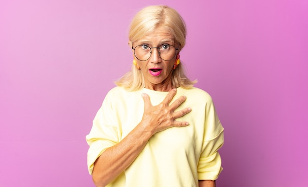 Vrouw van middelbare leeftijd die zich geschokt en verrast voelt, glimlacht, de hand ter harte neemt, blij is degene te zijn of dankbaarheid toont