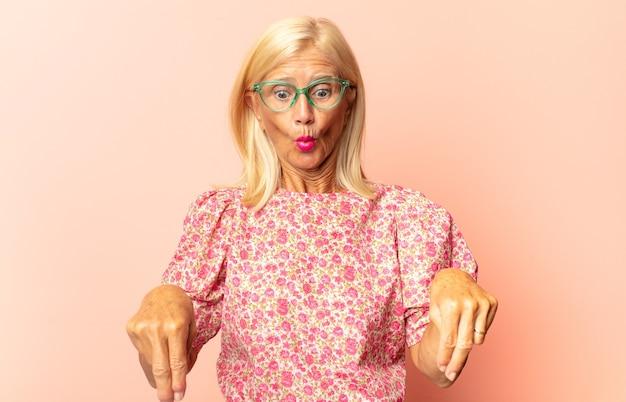 Vrouw van middelbare leeftijd die zich geschokt en verrast voelt, glimlacht, hand ter harte neemt, blij is om degene te zijn of dankbaarheid toont