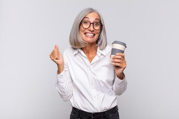 Vrouw van middelbare leeftijd die zich geschokt, opgewonden en gelukkig voelt, lacht en succes viert, zeggend wow! koffie concept