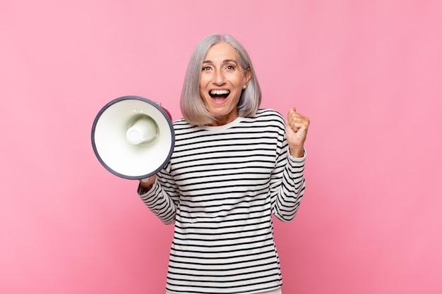 Vrouw van middelbare leeftijd die zich geschokt, opgewonden en gelukkig voelt, lacht en succes viert, zeggend wow! met een megafoon