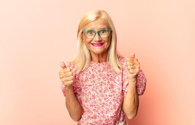 Vrouw van middelbare leeftijd die zich geschokt, opgewonden en gelukkig voelt, lacht en succes viert, zeggend wow!