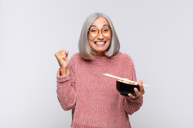 Vrouw van middelbare leeftijd die zich geschokt, opgewonden en gelukkig voelt